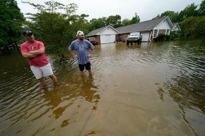 Danny González y Bob Neal atraviesan su vecindario inundado de agua después de pasar la tormenta tropical Claudette en Nueva Orleans.