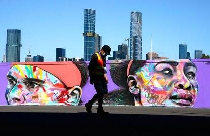 Un trabajador con mascarilla pasea ante un grafiti de Nadal y Serena.