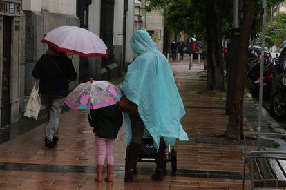 Una mujer y una niña pasean con paraguas en la capital en un día de lluvia.