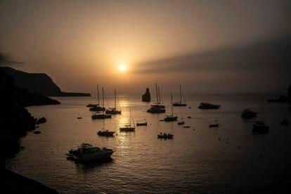 Barcos fondeados al tardecer en la cala Benirrás, Ibiza.