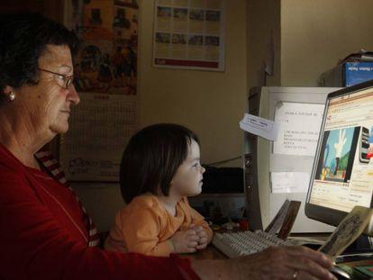 Una abuela con su nieta, ante el ordenador.