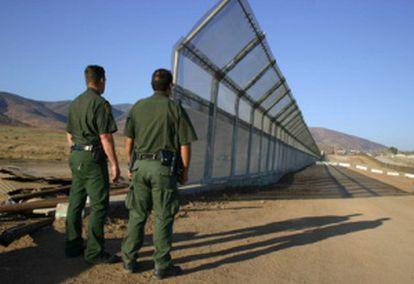 Dos policías vigilan la frontera de México con EE UU.
