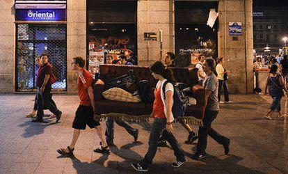 Varios jóvenes transportan por la calle del Carmen uno de los sofás del campamento de Sol.