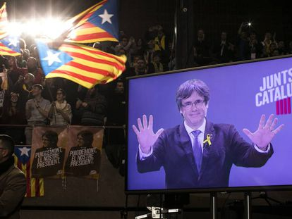 El expresidente de la Generalitat, Carles Puigdemont, aparece en una pantalla durante un mitin de Junt pel Si en Barcelona, el pasado 15 de diciembre.
