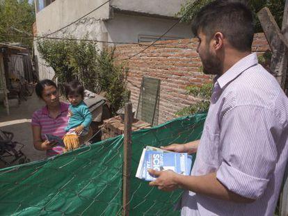 Un joven militante peronista entrega la papeleta de Scioli a una vecina del barrio Obligado de Bella Vista, en el Gran Buenos Aires.