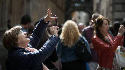 Turistas hacen fotografías con sus teléfonos móviles, en Barcelona.