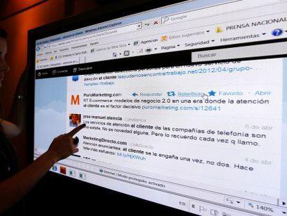 Una joven, ante una pantalla con comentarios en la red social Twitter.