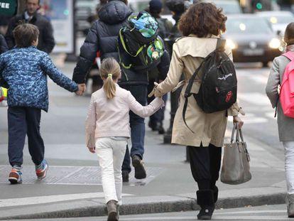 Una madre acompaña a sus hijos al colegio, en una imagen de archivo.