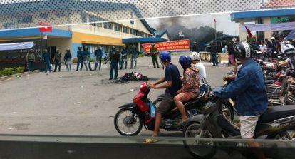 Motoristas pasan ante los policías que vigilan la zona donde se encuentra una factoría incendiada en la provincia vietnamita de Binh Duong.