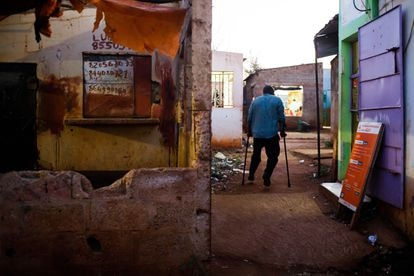 Manuel Joâo walks on his crutches through the center of Massaca, a town in southern Mozambique.