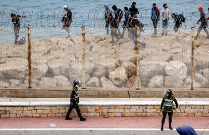 Agentes de seguridad marroquíes montan guardia mientras un grupo de migrantes caminan por la costa en la ciudad norteña de Fnideq, en un intento de cruzar la frontera, este martes.