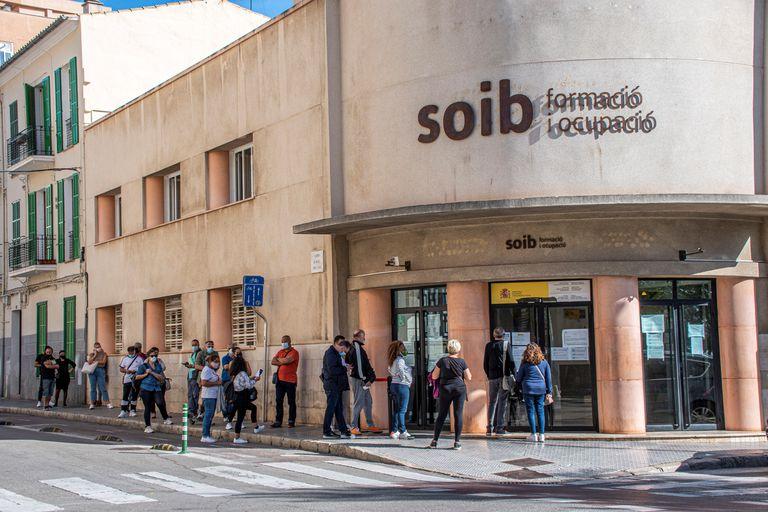 Varias personas hacen cola ante una oficina de empleo en Palma de Mallorca.