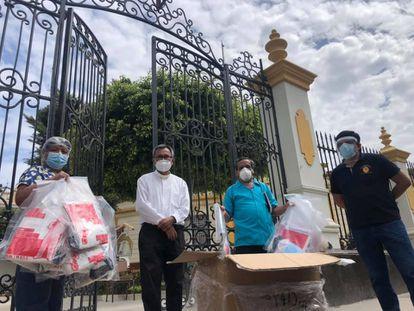 El párroco José Manuel Zamora y el fiscal Juan Carrasco entregan alimentos en Chiclayo, en Perú, en mayo.