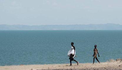 Dos personas caminan junto al lago Turkana, el mayor lago situado en un desierto del mundo, en el norte de Kenia.