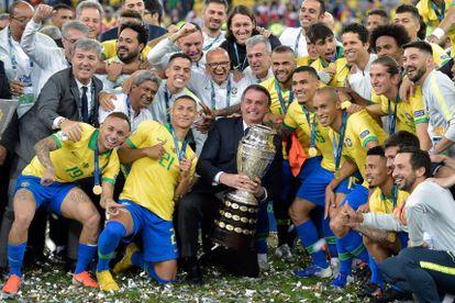 Jair Bolsonaro sostiene la Copa América junto a la selección de Brasil en la edición de 2019.