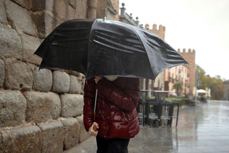 Una persona se protege de la lluvia este martes en Ávila.