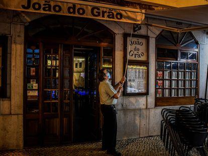 Un camarero cierra las persianas de un restaurante en el centro de Lisboa el 9 de noviembre de 2020.