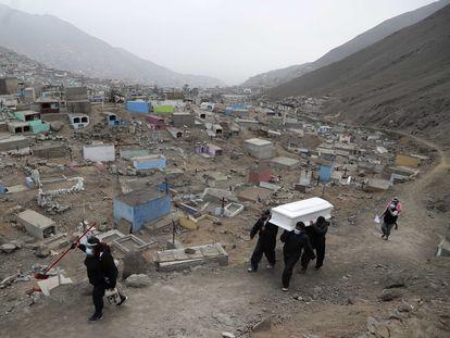 Trabajadores de un cementerio en las afueras de Lima cargan un ataúd, el pasado mes de agosto.