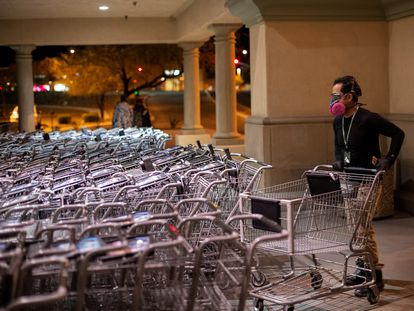 Un hombre con mascarilla apila carritos de supermercado.