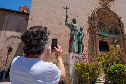 Un hombre fotografía una pintada crítica en el monumento dedicado al fraile Junípero Serra en Palma de Mallorca, el 22 de junio de 2020.