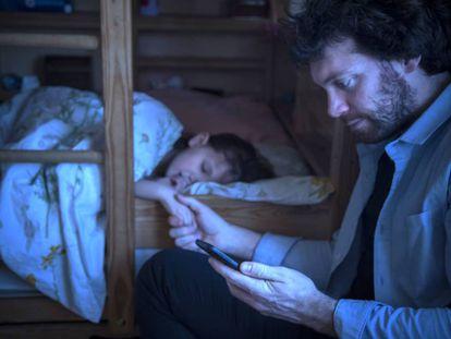 Un padre consulta el móvil.