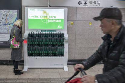 Una chica saca un paraguas, que se paga por horas, de un dispensador situado en una parada de metro de Shanghái.