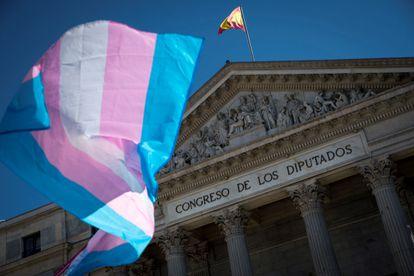 Una bandera del orgullo trans ondea ante el Congreso de los Diputados en junio.