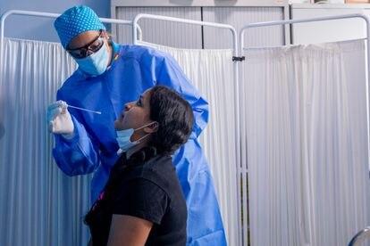 Un trabajador sanitario realiza un test PCR a una mujer en el Centro de Especialidades Carabanchel Alto.