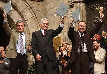 Los tres líderes, aplaudidos por el público a su salida del Salón del Tinell con el pacto en alto.