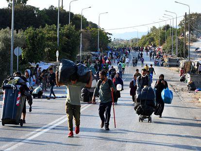 Migrantes del campo incendiado de Moria caminan hacia una nueva ubicación en la isla griega de Lesbos, el jueves.