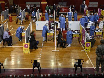 Trabajadores de la salud son vacunados con la Sputnik V en una cancha de baloncesto en Buenos Aires.