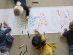 Cuatro niños pintan un cartel.