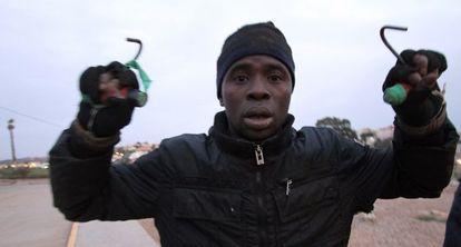 Un inmigrante en la valla de Melilla, este martes.