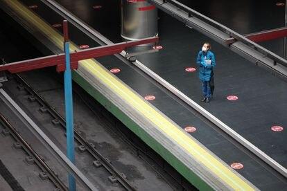 Una mujer con mascarilla espera el metro en Madrid, el viernes.