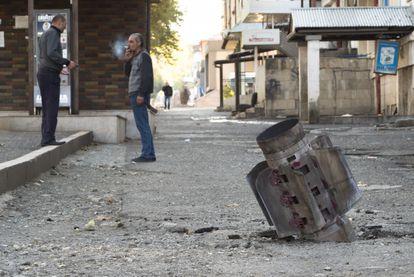 Dos hombres conversan este lunes en una calle de Stepanakert alcanzada por la artillería.
