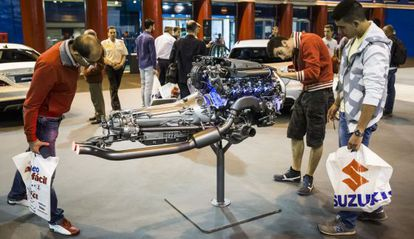 Varias personas observan un motor en el Salón del Automóvil de Madrid