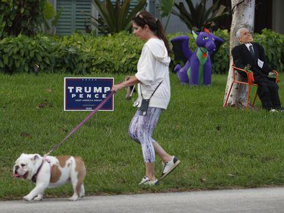 Una mujer pasea a su perro en una calle de Miami, este sábado 31 de octubre.