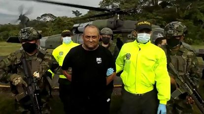 """Handout video grab released on October 23, 2021 by the Colombian Army press office showing members of the Colombian Army and police escorting Colombia's most-wanted drug lord and head of the Gulf Clan, Dairo Antonio Usuga (C) -alias 'Otoniel'- after his capture, in Bogota. - Usuga, for whom the United States offered a reward of five million dollars, was captured by Colombian authorities, in Necocli, Antioquia department, the government reported. (Photo by Handout / Colombian army / AFP) / RESTRICTED TO EDITORIAL USE - MANDATORY CREDIT """"AFP PHOTO / COLOMBIAN ARMY """" - NO MARKETING - NO ADVERTISING CAMPAIGNS - DISTRIBUTED AS A SERVICE TO CLIENTS"""