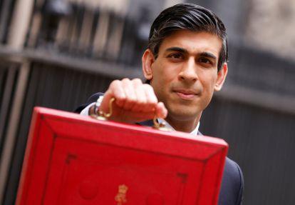 """El ministro de Economía del Reino Unido, Rishi Sunak, presenta este miércoles en Downing Street el """"maletín rojo"""" de los presupuestos."""