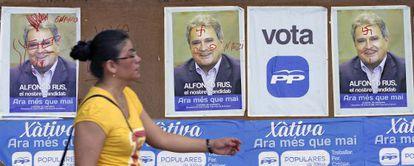 Una vecina pasa por delante de los carteles electorales de Alfonso Rus colocados en la noche del jueves en Xàtiva.