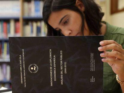 Una mujer lee un ejemplar de la tesis doctoral de Pedro Sánchez que se encuentra en la Universidad Camilo José Cela. ULY MARTIN.