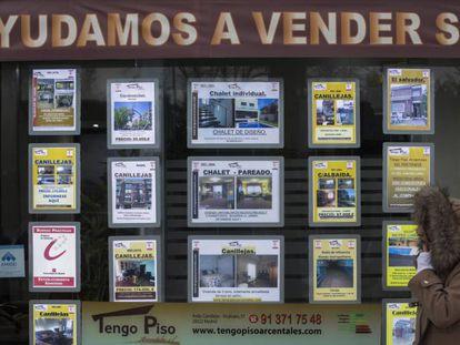 Una mujer pasa junto a una inmobiliaria en Madrid.