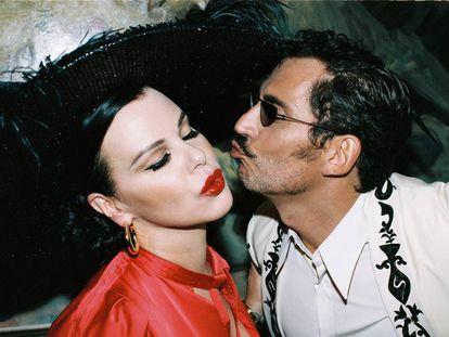La protagonista de 'Arde Madrid', Debi Mazar, recibe el beso del director de la serie, Paco León. Ella lleva pendientes Aristocrazy, vestido Self-Portrait para Mytheresa y tocado Betto García. Él viste camisa y chaqueta Dries Van Noten y sello Bárcena.