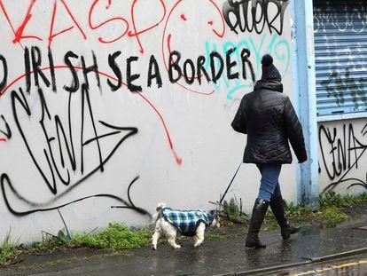 """Una mujer camina frente a una pared en la que se lee """"Sin frontera del mar de Irlanda"""", en Belfast el miércoles."""