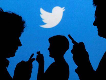 Usuarios de móviles ante el logo de Twitter.