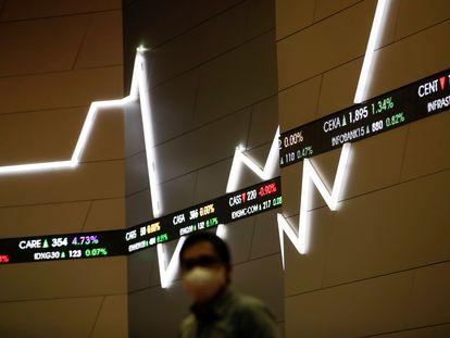 Un hombre protegido con mascarilla, ante un panel informativo de la Bolsa de Indonesia.
