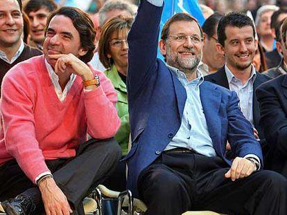 Rajoy saluda con la señal de la victoria junto a Aznar en el mitin de León.