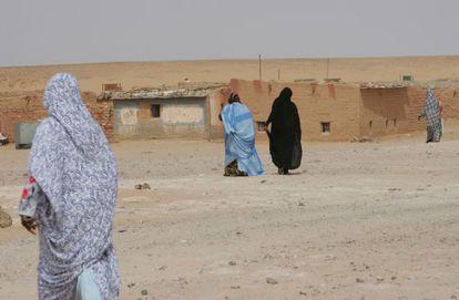 Varias mujeres caminan hacia sus casas de adobe en el campo de refugiados de los saharauis del en Tinduf (Argelia).