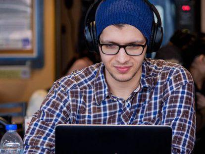 Un joven practica inglés con su ordenador en una cafetería.