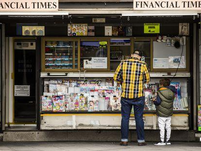 Un padre, con su hijo, en un kiosco de prensa en las inmediaciones del hospital de La Paz de Madrid.